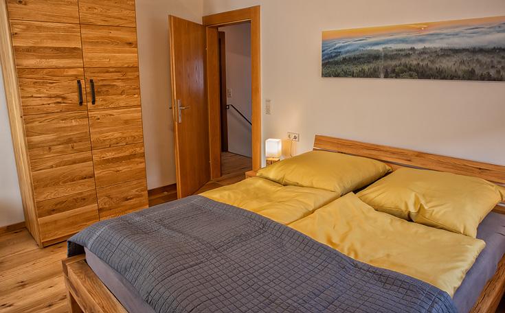 Ferienhaus Enztalblick in Enzklösterle im Nordschwarzwald - Das Schlafzimmer im Obergeschoss mit Schrank und Bett aus massivem Eichenholz