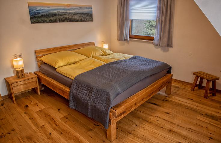 Ferienhaus Enztalblick in Enzklösterle im Nordschwarzwald - Das Schlafzimmer im Obergeschoss mit Balkenbett aus massivem Eichenholz