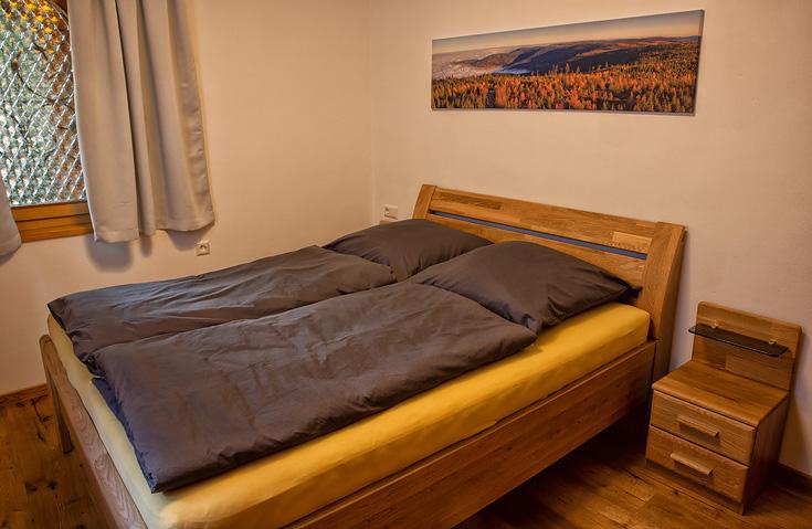 Ferienhaus Enztalblick in Enzklösterle im Nordschwarzwald - Das Schlafzimmer im Erdgeschoss mit Bett aus massivem Buchenholz