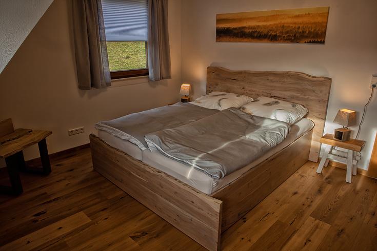 Ferienhaus Enztalblick in Enzklösterle im Nordschwarzwald - Das Schlafzimmer im Obergeschoss mit Massivholzbett aus Akazienholz